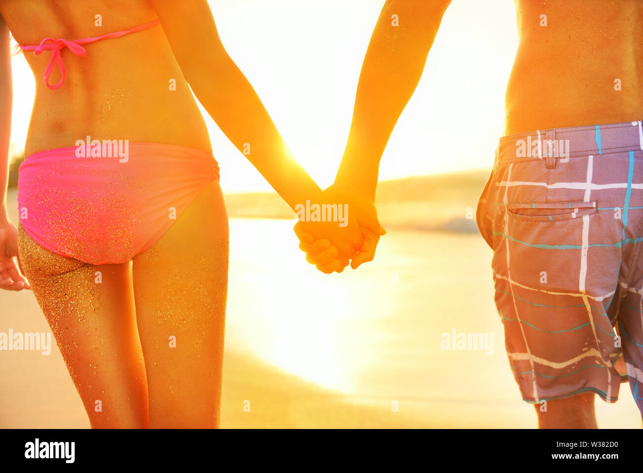Holding hands couple in swimwear at beach. Rear view of fit couple's buttocks and legs as weight loss concept at beach sunset during summer vacations. Stock Photo