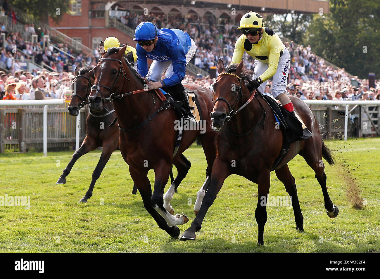 Dubai Tradition ridden by jockey Hector Crouch (left) wins the Maritime Cargo Handicap as Apparate ridden by jockey Andrea Atzeni (right) finishes second during day three of the Moet and Chandon July Festival 2019 at Newmarket Racecourse. - Stock Image