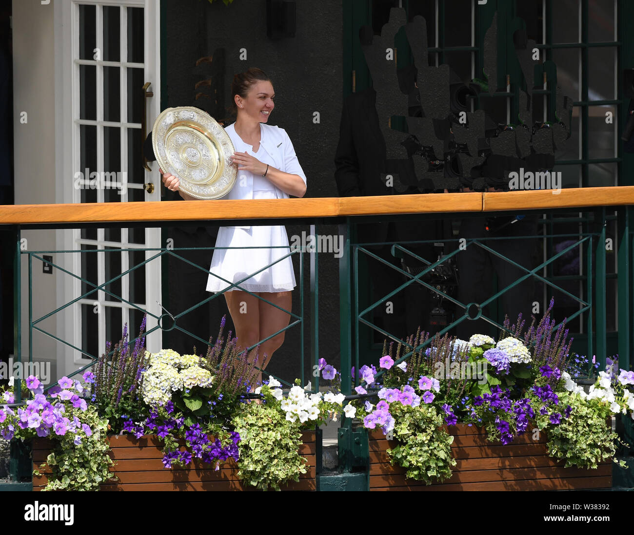 London, UK. 13th July, 2019. The Championships Wimbledon 2019 13072019 Simona Halep shows the winners trophy  the Venus Rosewater Dish  to the crowds from the members balcony after she wins Ladies Singles Final Photo Roger Parker International Sports Fotos Ltd/Alamy Live News - Stock Image