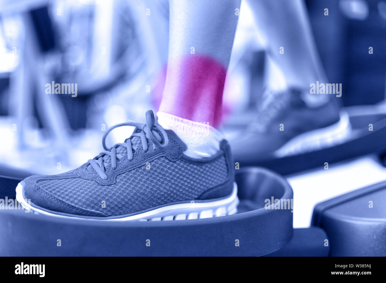 Hurting ankles - pain caused by fitness injury. Closeup of leg with red circle showing painful area of female athlete training on elliptical exercise machine. Sprained ankle concept. - Stock Image