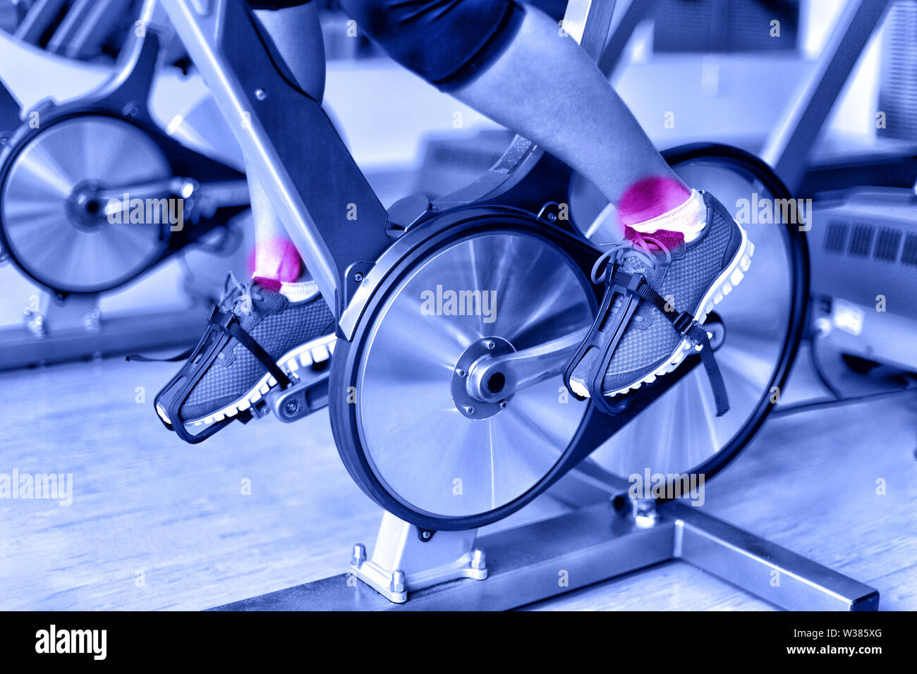 Sports injury - ankle pain during training on spinning bike at gym. Closeup of female athlete's legs using bicycle machine at fitness center in blue monochromatic filter. - Stock Image