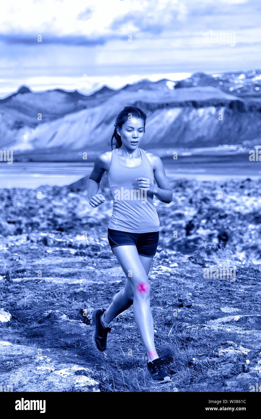 Sports woman portrait showing joints injuries. Active fitness lifestyle can cause ankle and knee sprains showed by red circles on body of female trail runner in nature. Blue monochrome filter. - Stock Image