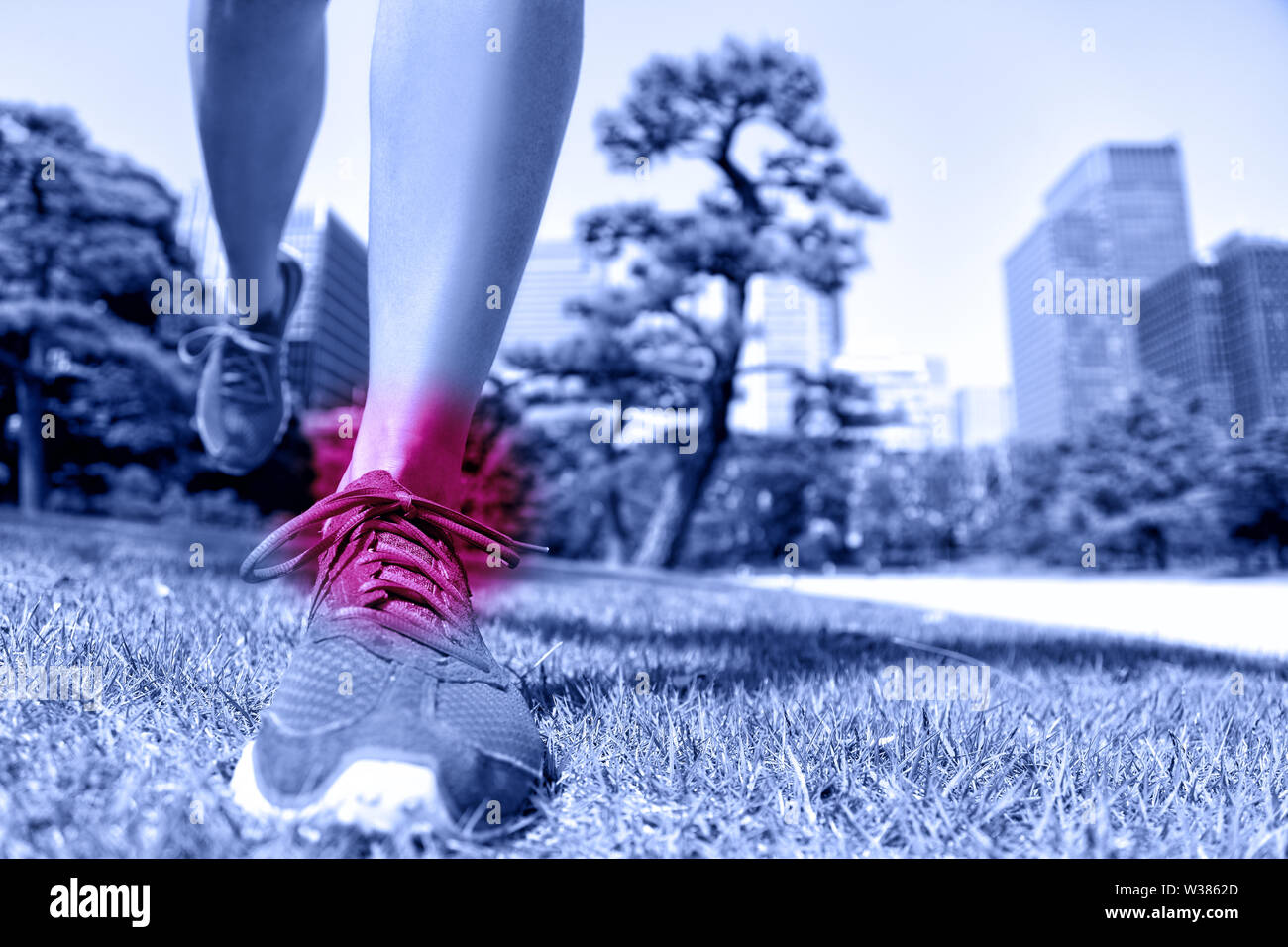 Sports injury - runner feet with ankle pain. Closeup of running shoes landing on soft grass with red circle showing hurting joints and ligaments caused by a fitness trauma. - Stock Image
