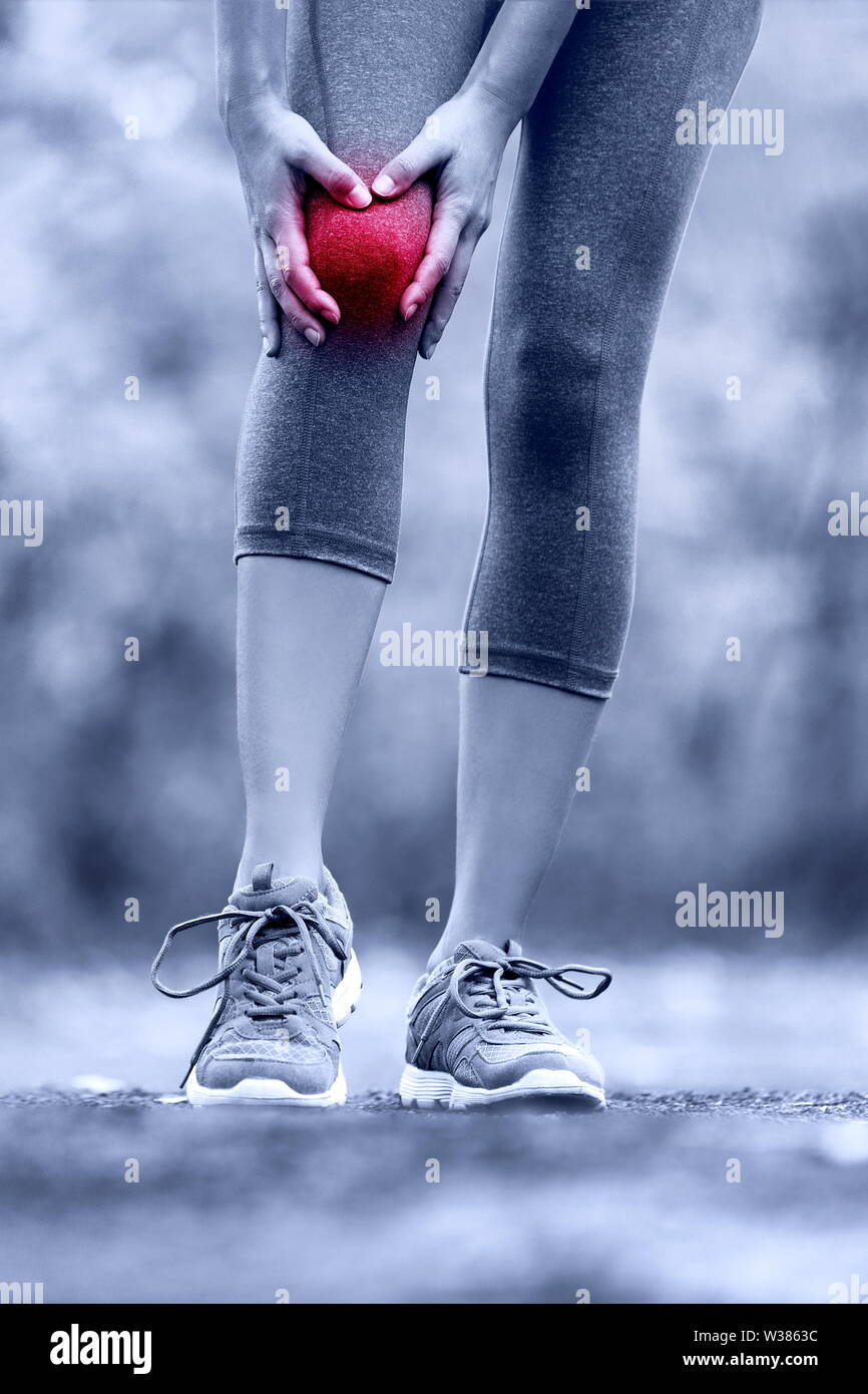 Knee injury - runner with sprained leg joint pain. Closeup of female athlete's leg with red circle showing pain. Woman holding with hands around hurting knee in summer nature background. - Stock Image