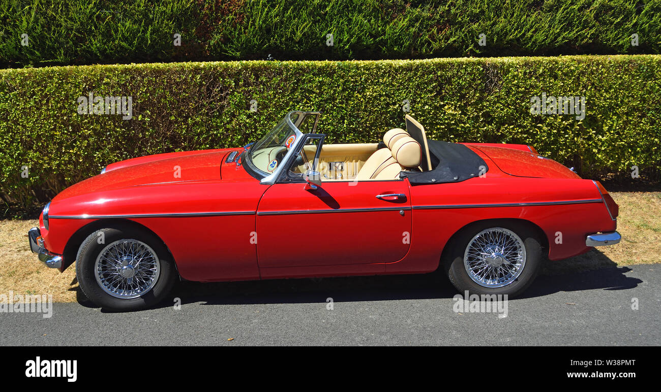 Classic Red MG Open Top Sports Car Parked by hedge. - Stock Image