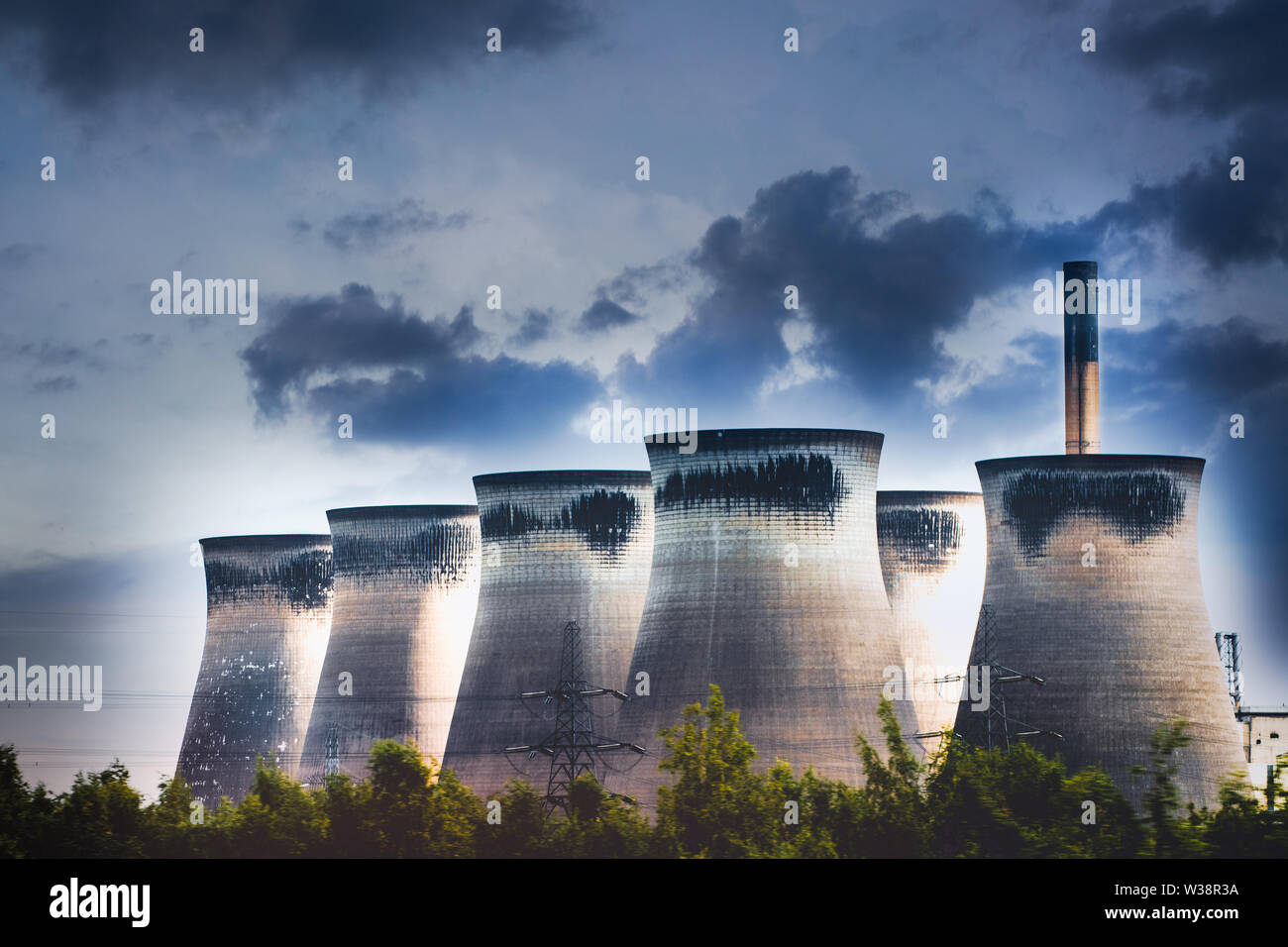 Energy Power Plant chimneys and cooling towers with dramatic sky. Polluting clean air showing climate change concepts...global warming Stock Photo