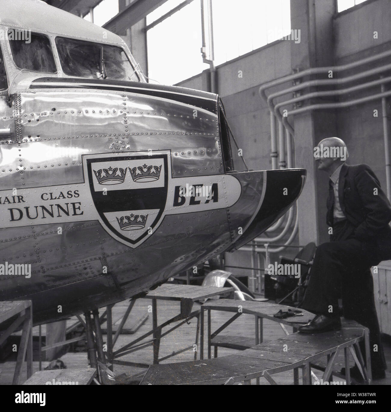 1960s, historical, man in hanger looking at the stainlees steel front or nose of a BEA aircraft, Dunne, a Douglas DC-3, England, UK. - Stock Image