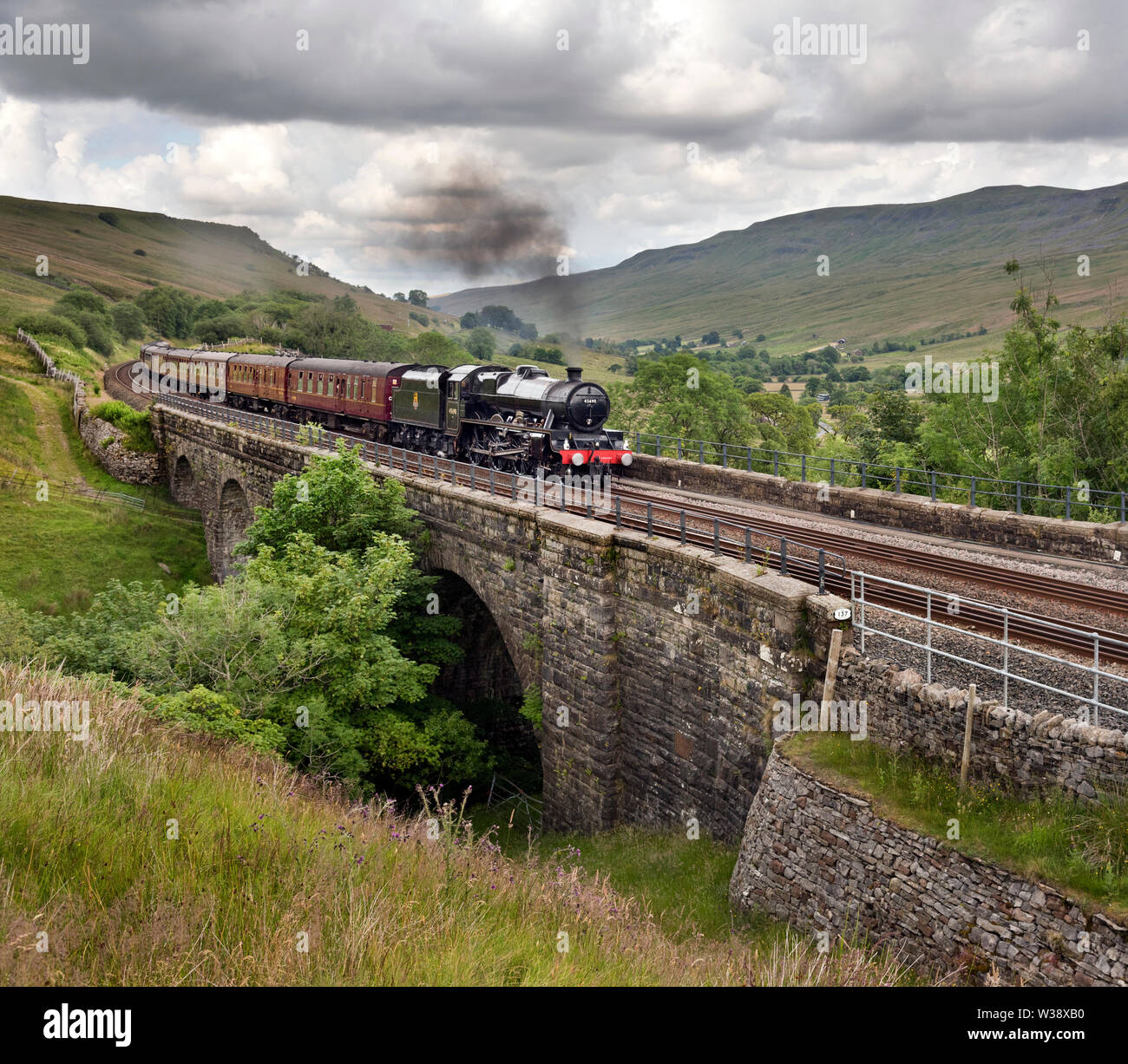 Cumbria, UK. 13th July, 2019. Steam locomotive 'Leander' hauls the Cumbrian Mountain Express special up the gradient to Ais Gill summit heading south on the Settle-Carlisle railway line. Steam specials over the route are a fairly regular fixture over the Summer period. Credit: John Bentley/Alamy Live News - Stock Image