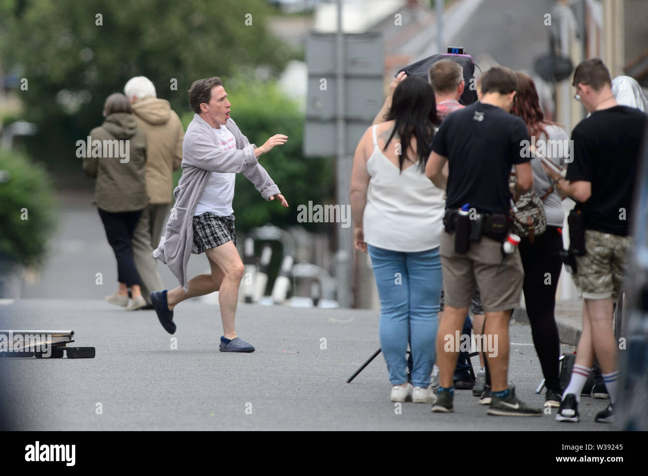 """Barry, UK. 13th July, 2019. """"Uncle Bryn"""" played by Rob Bryden films a scene for the BBC comedy Gavin & Stacey Christmas special in Trinity Street, Barry, South Wales. Credit: Mark Lewis/Alamy Live News Stock Photo"""