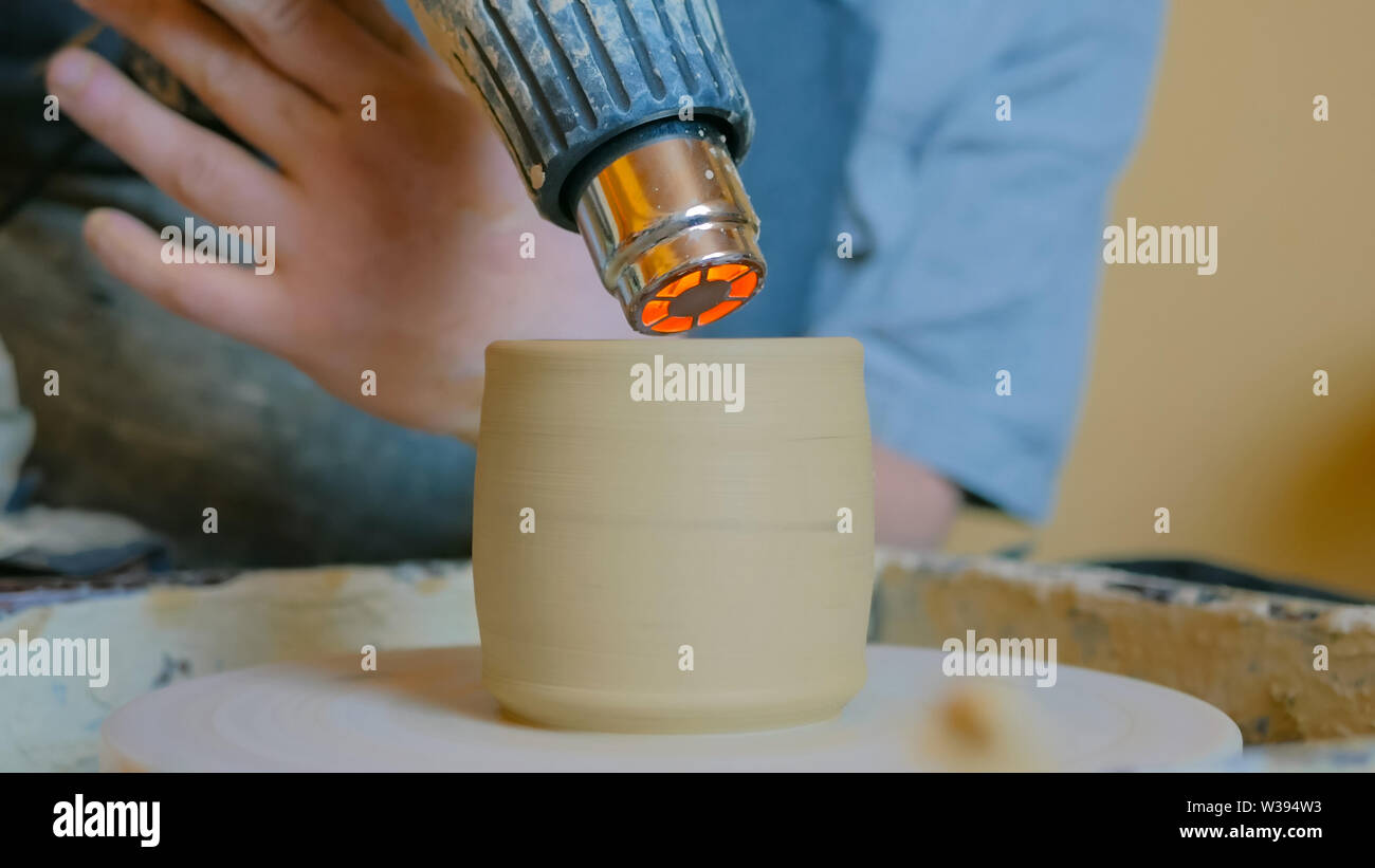 Potter drying ceramic pot with special dryer - Stock Image