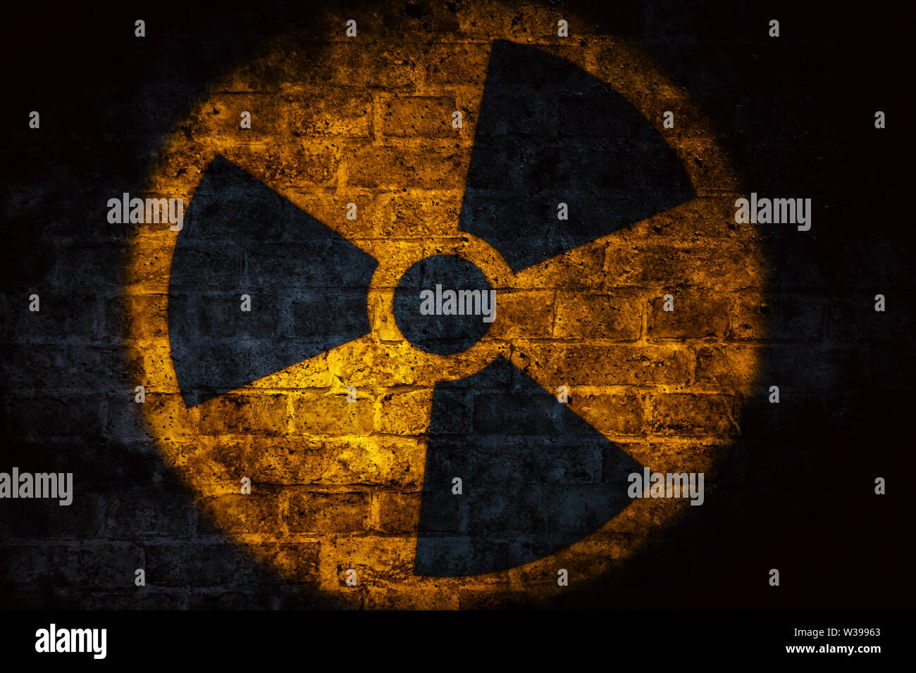 Nuclear energy radioactive (ionizing atomic radiation) round yellow symbol shape painted on brick concrete cement wall texture dark background. Nuclea - Stock Photo