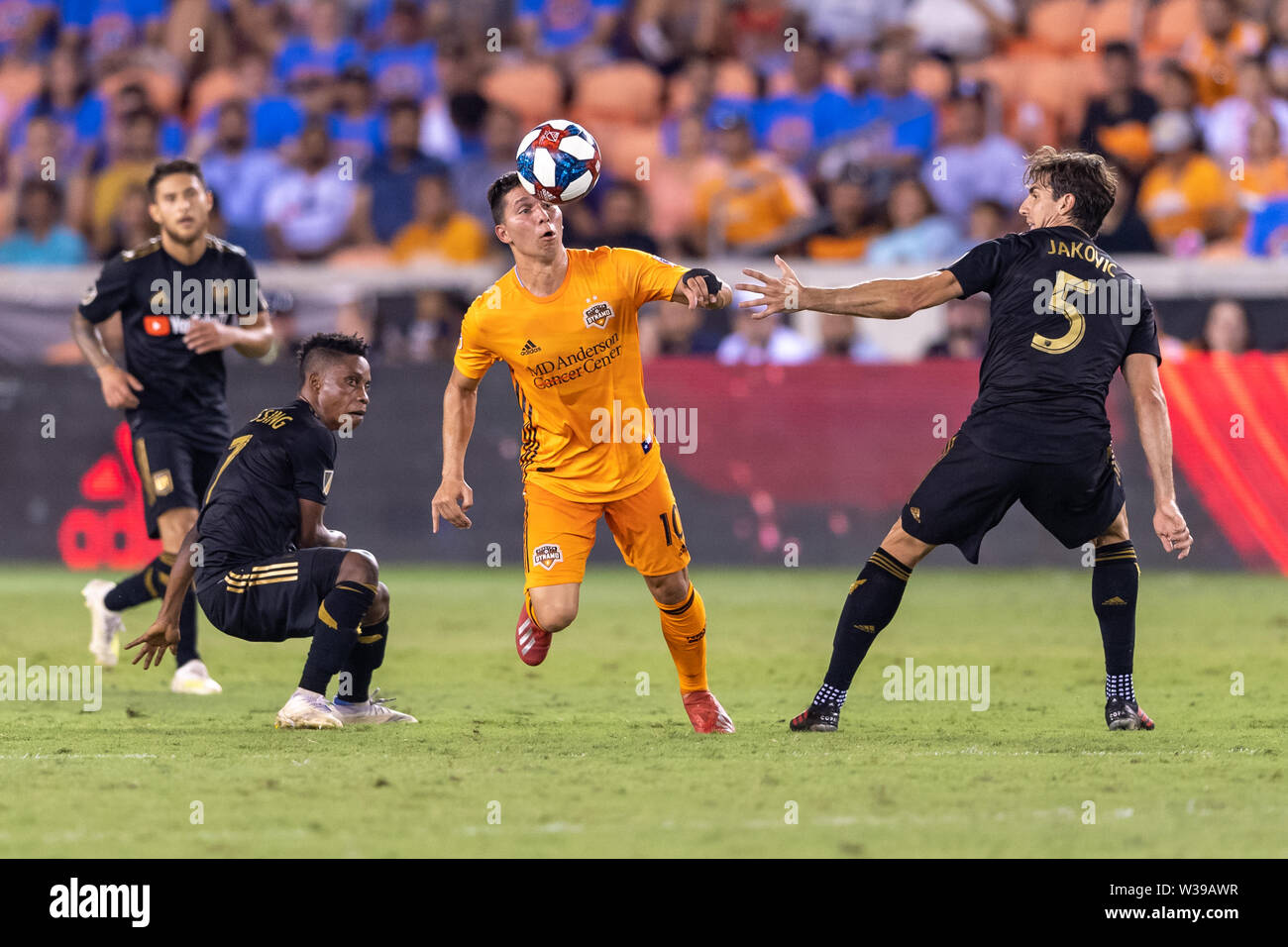 Houston, Texas, USA. 12th July, 2019. Houston Dynamo midfielder Tomas Martinez (10) looks to control the ball from Los Angeles FC defender Dejan Jakovic (5) and forward Latif Blessing (7) during a match between Los Angeles FC and Houston Dynamo at BBVA Stadium in Houston, Texas. The final LAFC wins 3-1. Maria Lysaker/CSM/Alamy Live News - Stock Image