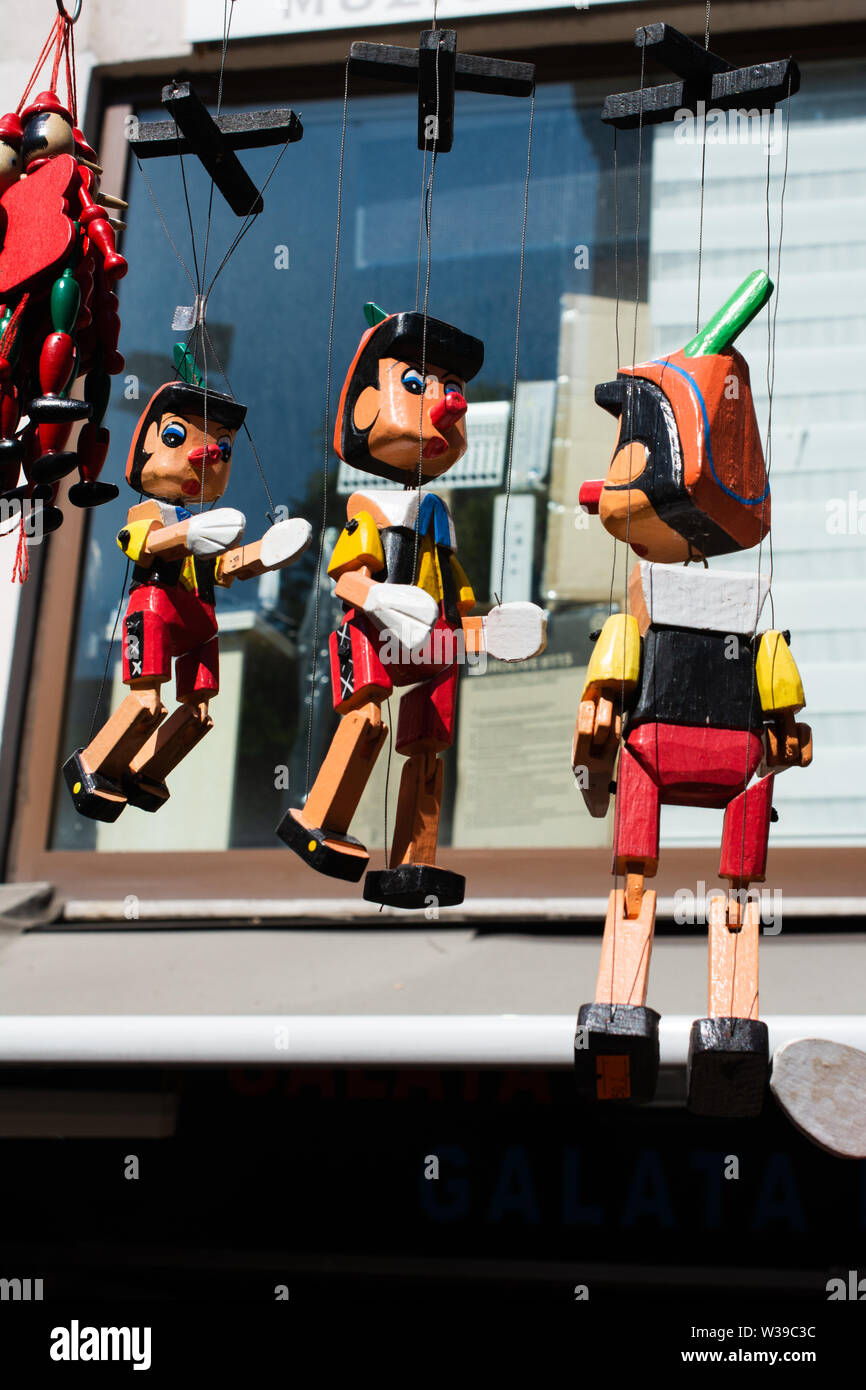 Wooden pinocchio dolls with long nose. Conceptual fairy tale character. - Stock Image