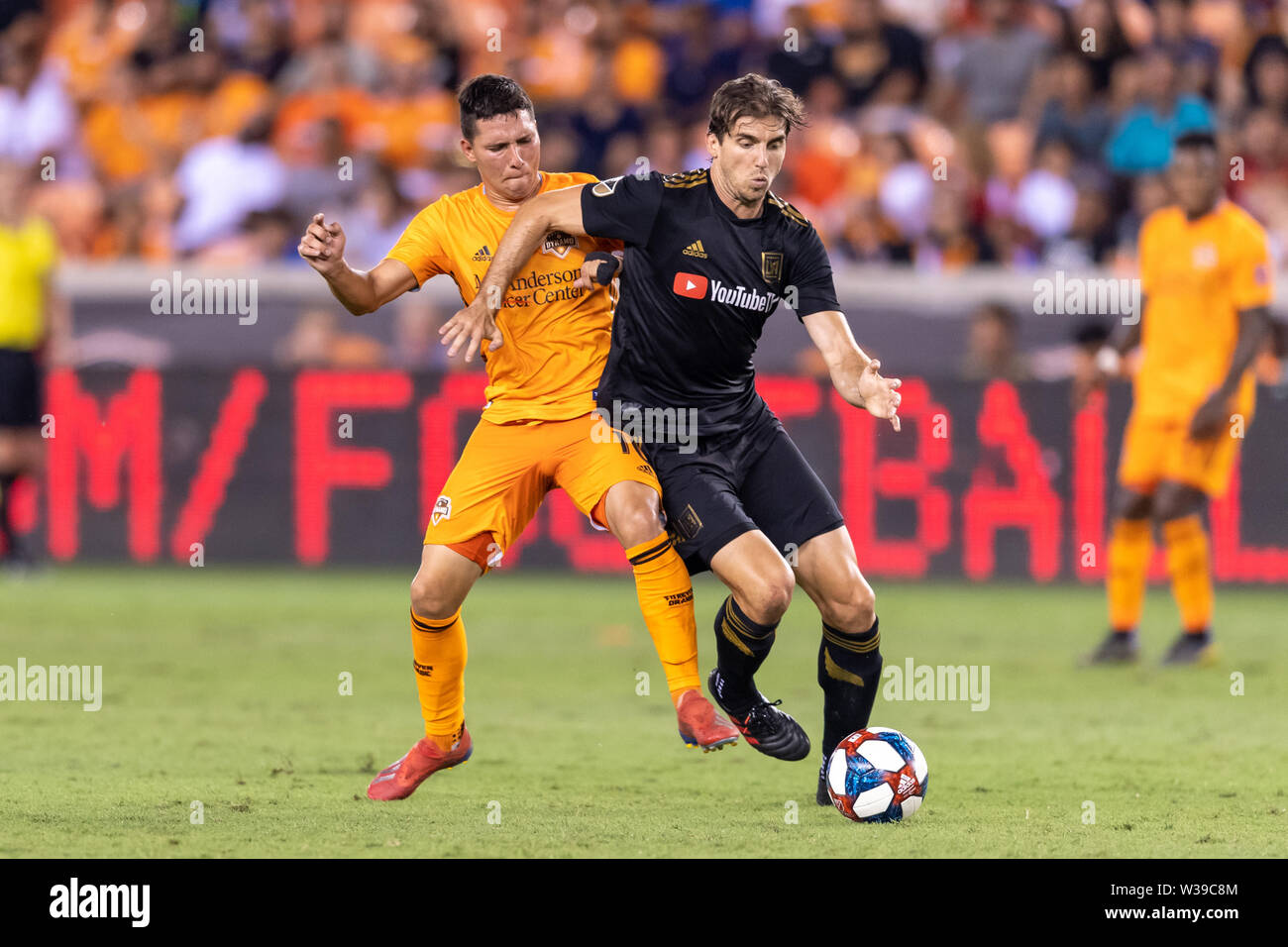 Houston, Texas, USA. 12th July, 2019. Houston Dynamo midfielder Tomas Martinez (10) looks to control the ball from Los Angeles FC defender Dejan Jakovic (5) during a match between Los Angeles FC and Houston Dynamo at BBVA Stadium in Houston, Texas. The final LAFC wins 3-1. Maria Lysaker/CSM/Alamy Live News - Stock Image