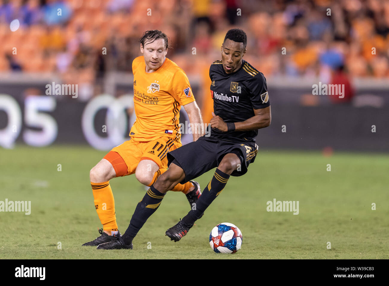 Houston, Texas, USA. 12th July, 2019. Los Angeles FC midfielder Mark-Anthony Kaye (14) and Houston Dynamo midfielder Thomas McNamara (11) during a match between Los Angeles FC and Houston Dynamo at BBVA Stadium in Houston, Texas. The final LAFC wins 3-1. Maria Lysaker/CSM/Alamy Live News - Stock Image
