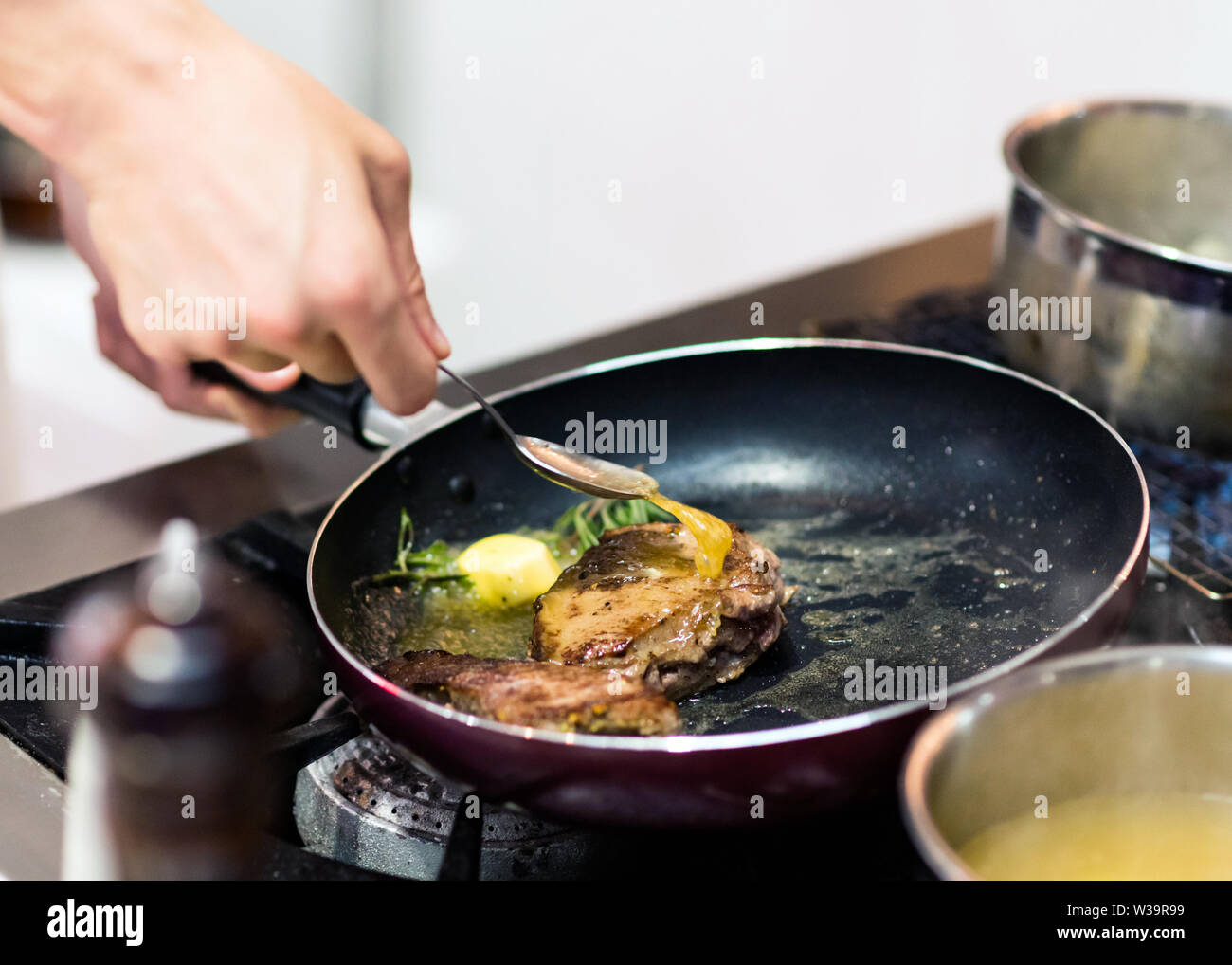 Chef cooking food in the kitchen, Chef preparing food - Stock Image