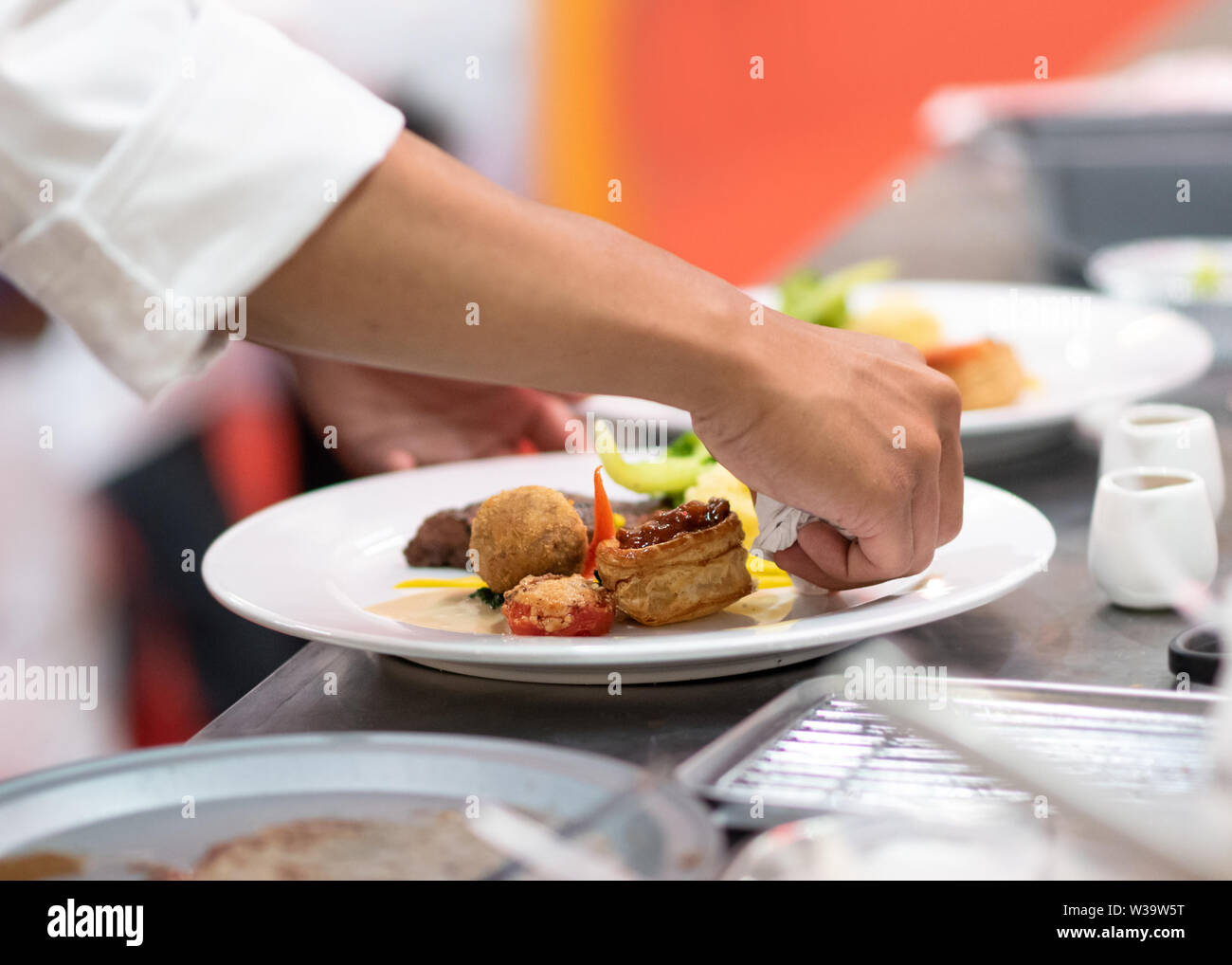 Chef preparing food, meal, in the kitchen, chef cooking, Chef decorating dish, closeup - Stock Image