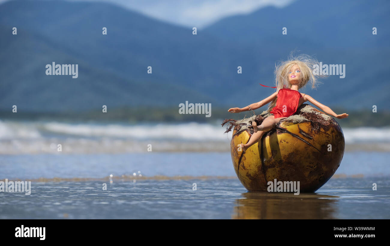 Australian beach scenes. Life's a beach in Australia, a Barbie doll relaxes in a coconut on Four Mile Beach in North Queensland. - Stock Image