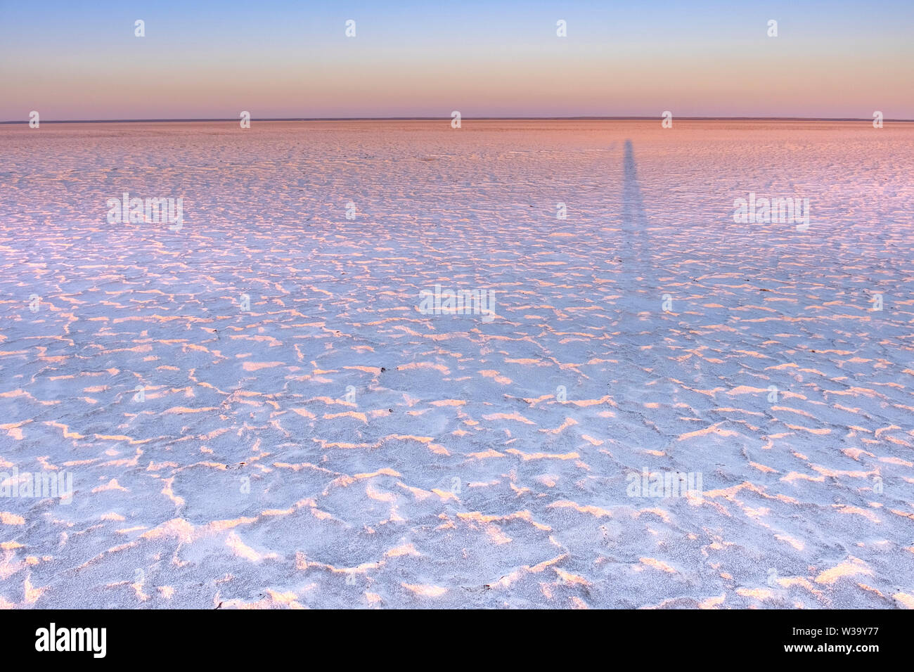 Sunset / Sunrise at white salt crusts on mud at the shore of the large, arid-zone Kati Thanda-Lake Eyre in outback in northern South Australia. - Stock Image