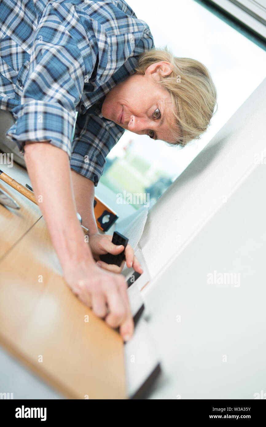 woman in the laying of wood laminate - Stock Image
