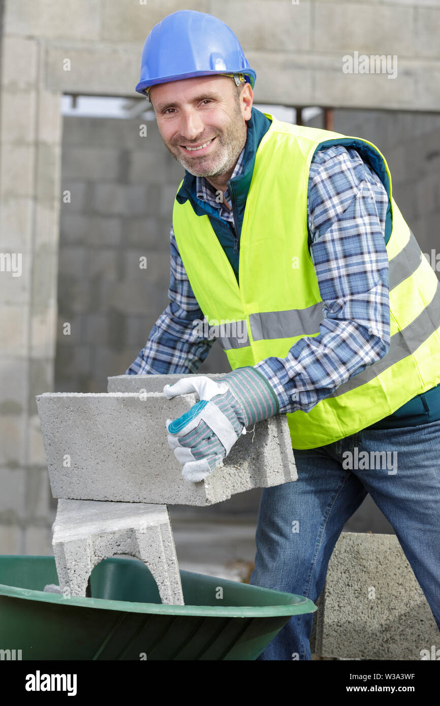 happy builder holding a cement bloc - Stock Image
