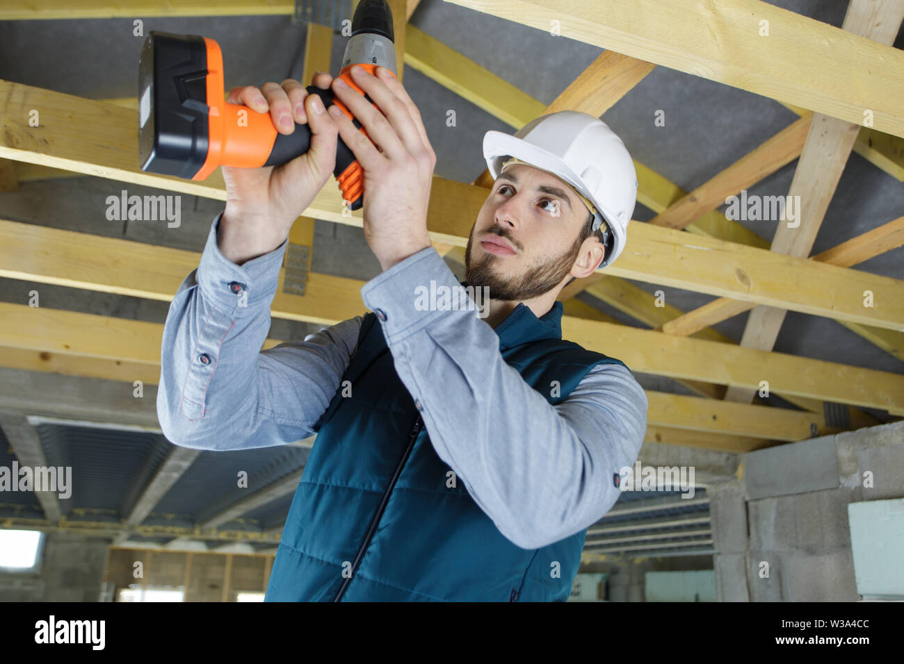 worker drilling wood beam during remodeling - Stock Image