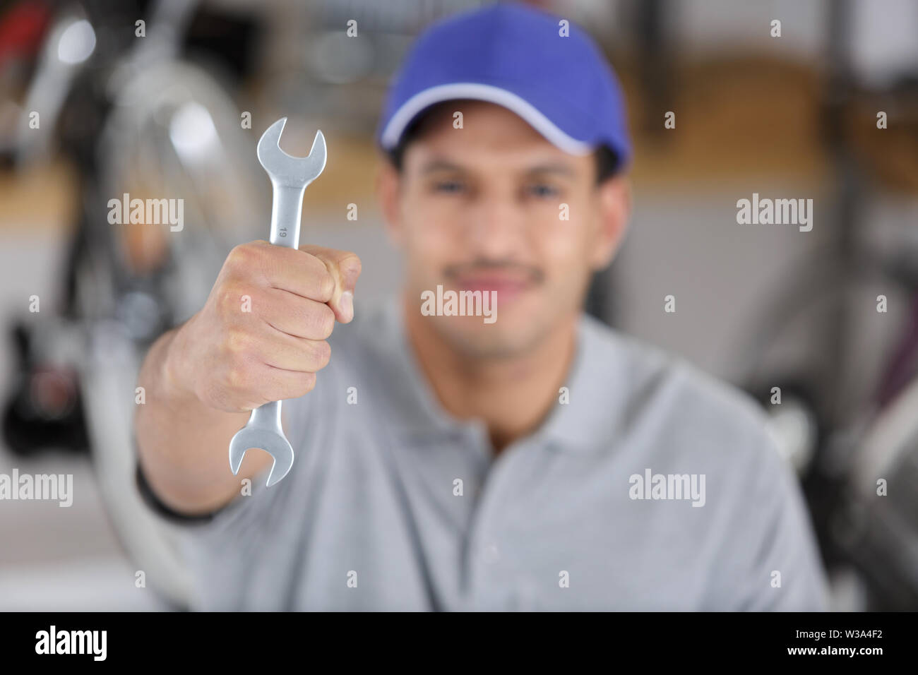 mechanic or plumber with spanners in hands - Stock Image