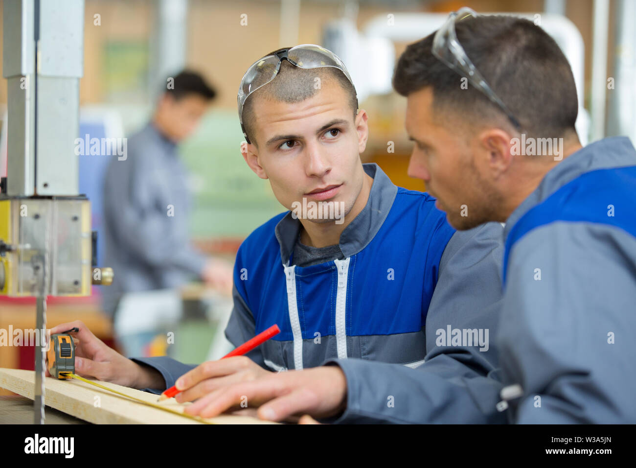 apprentice makes the measurements on the board - Stock Image