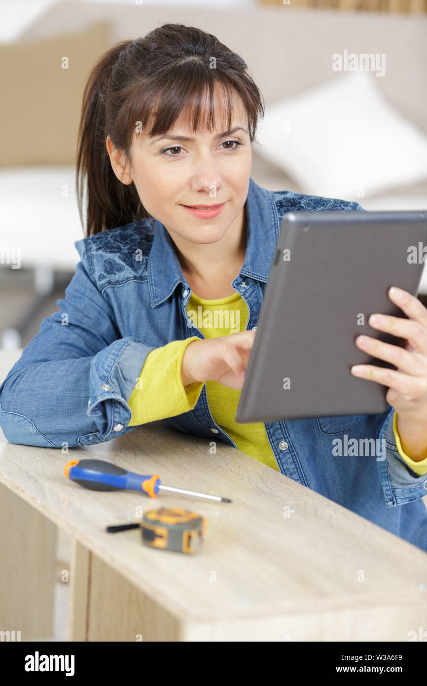 woman assembling of furniture using a tablet - Stock Image
