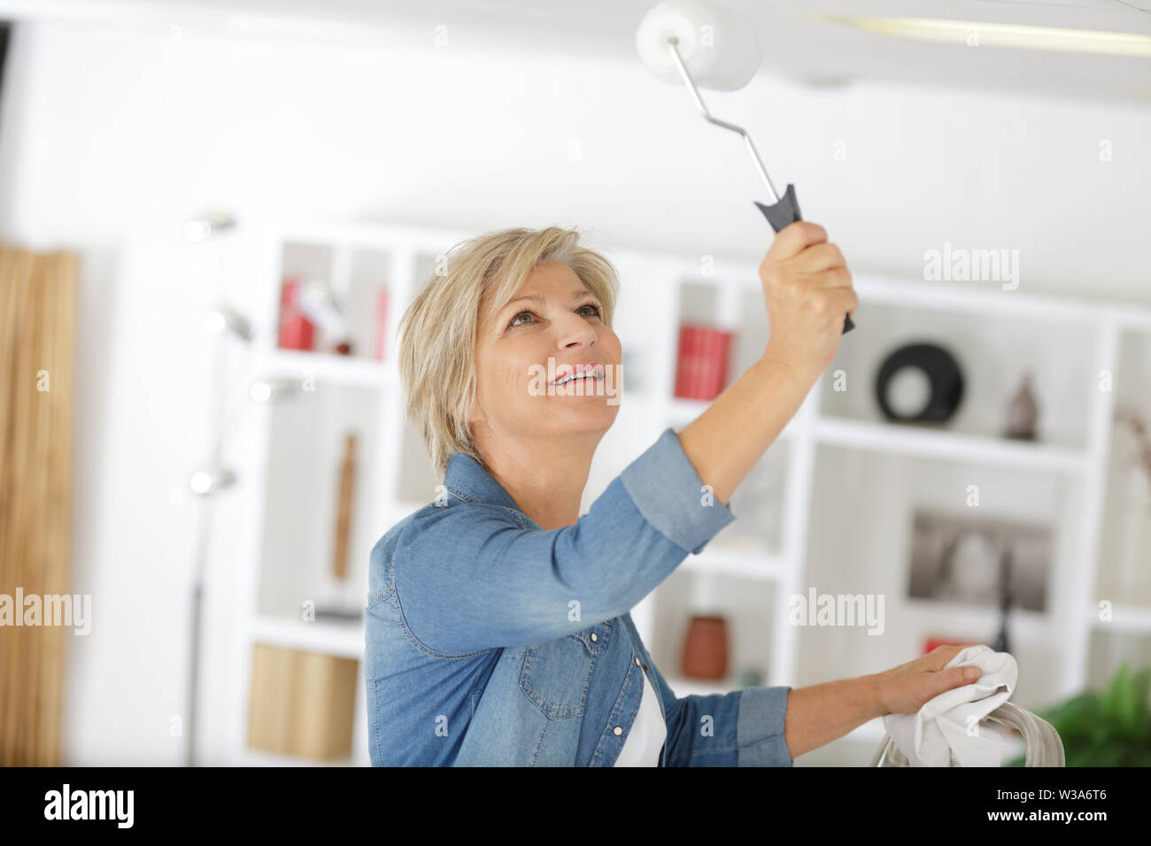 mature woman using roller to paint the ceiling - Stock Image