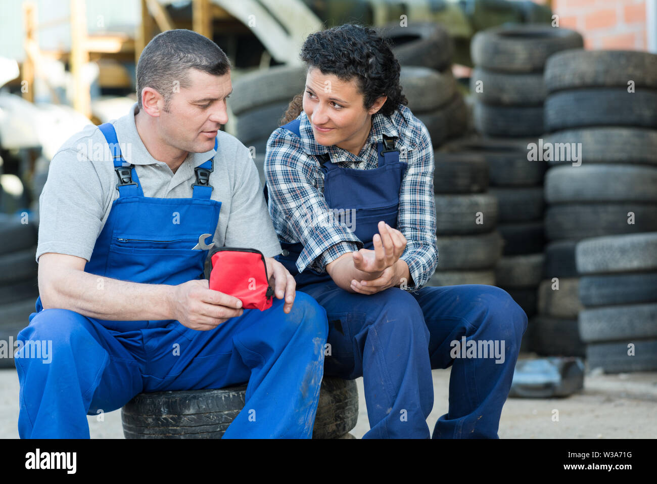 man and woman mechanic looking at arm injure - Stock Image