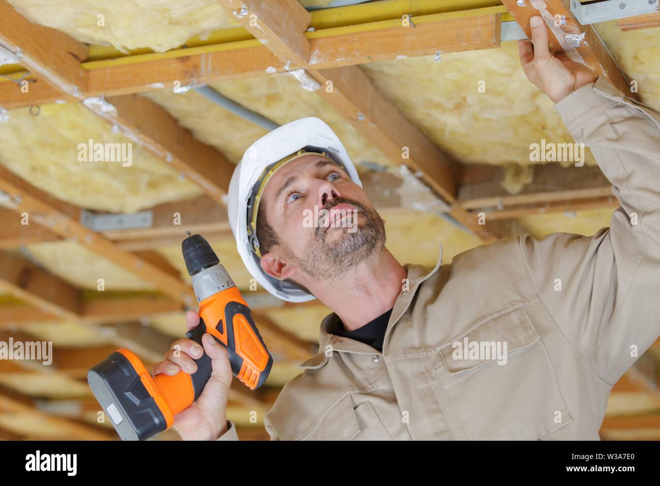 male builder using drill on wooden ceiling framework - Stock Image
