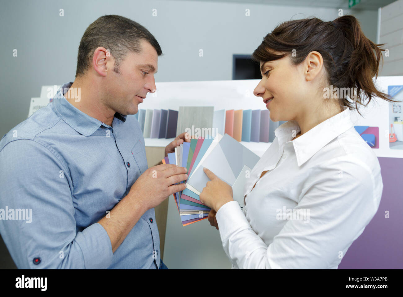 happy couple choosing color for their room together - Stock Image