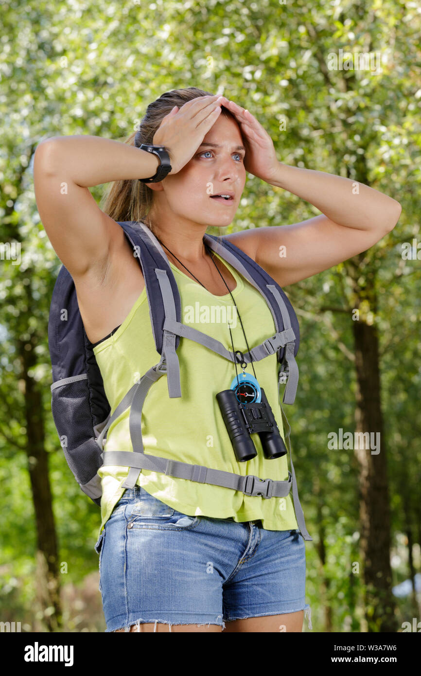 distressed female backpacker in countryside - Stock Image
