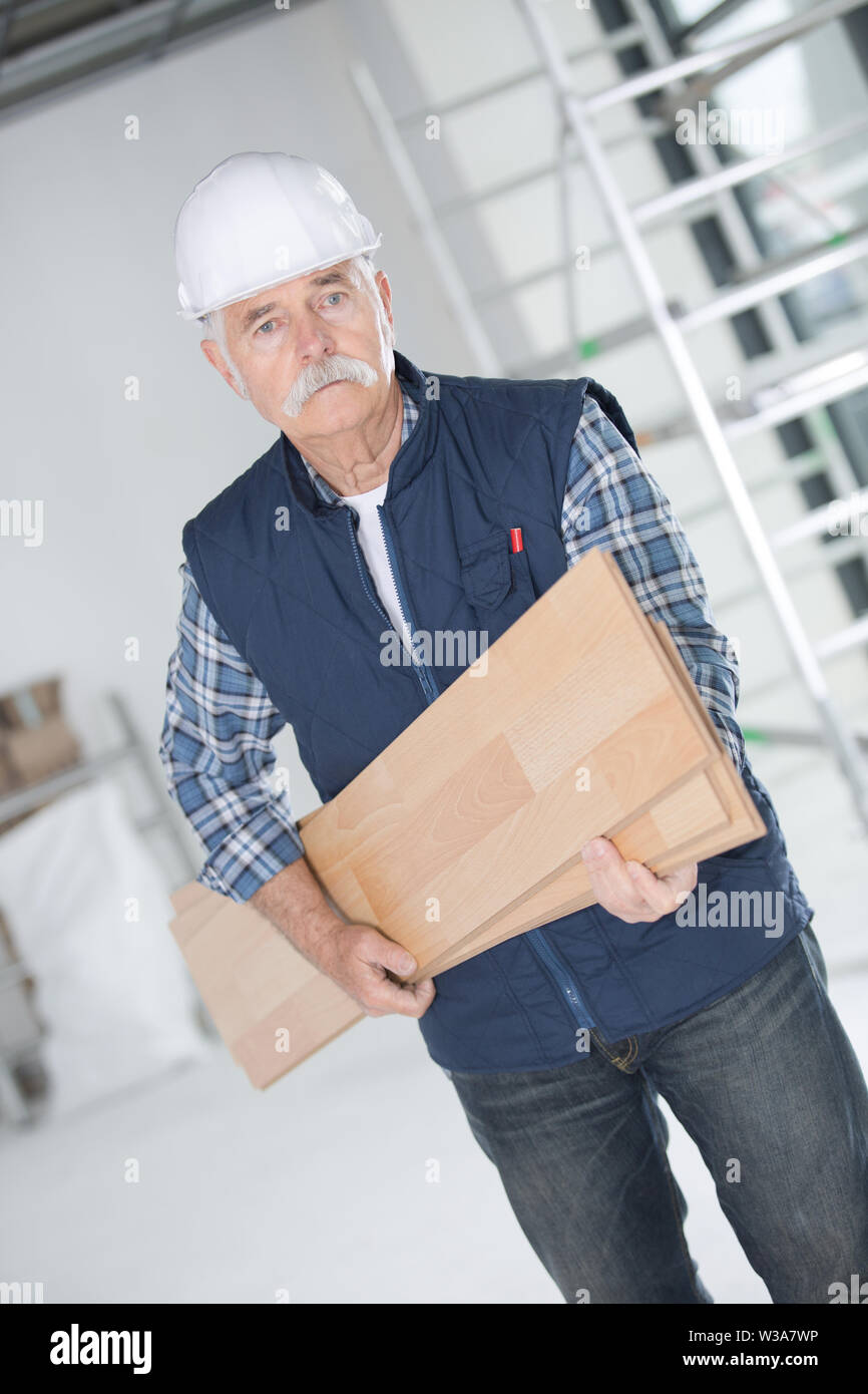 mature carpenter with wooden planks - Stock Image