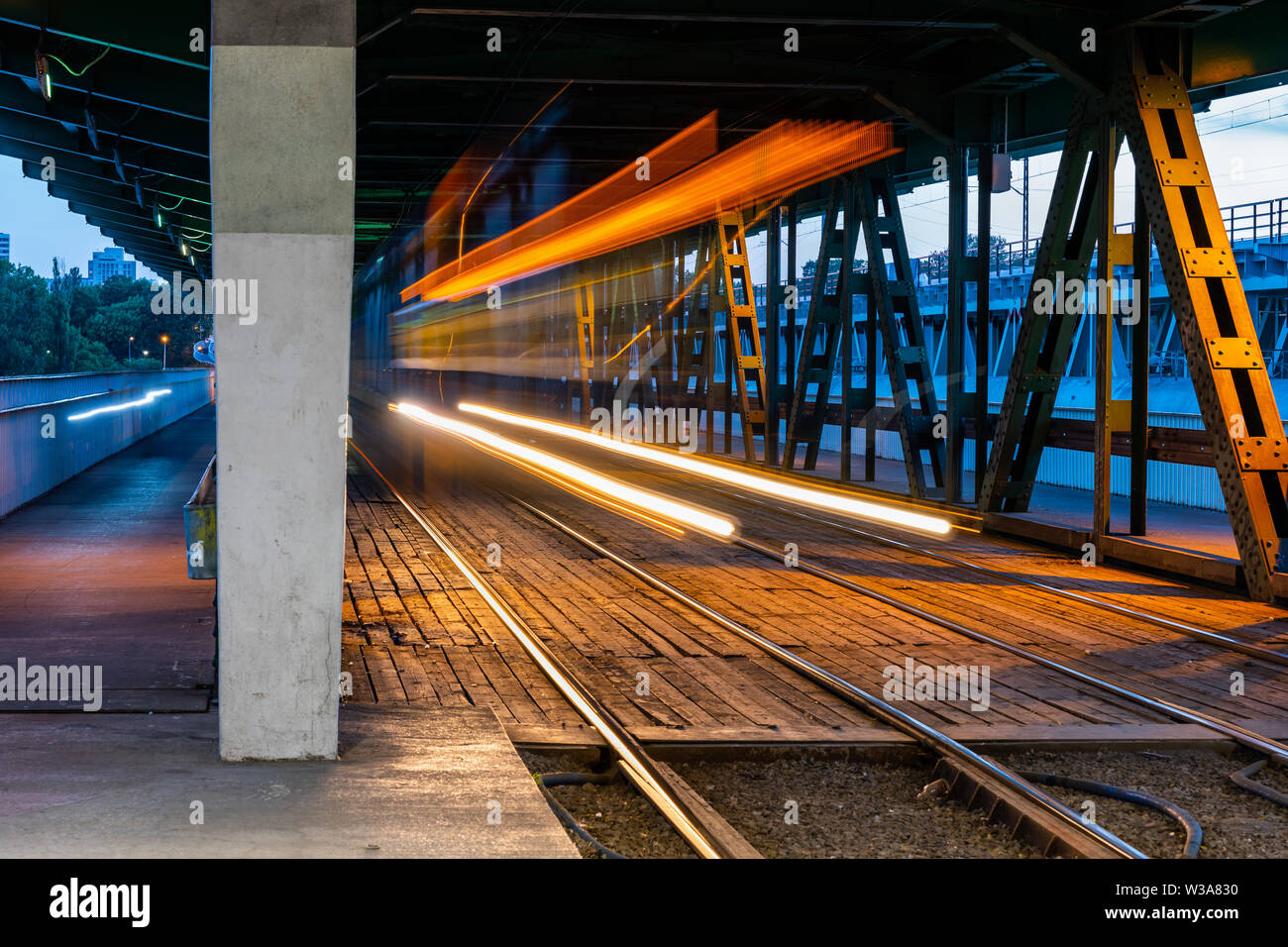Gdanski Bridge with tram light trails in the evening in Warsaw, Poland. - Stock Image