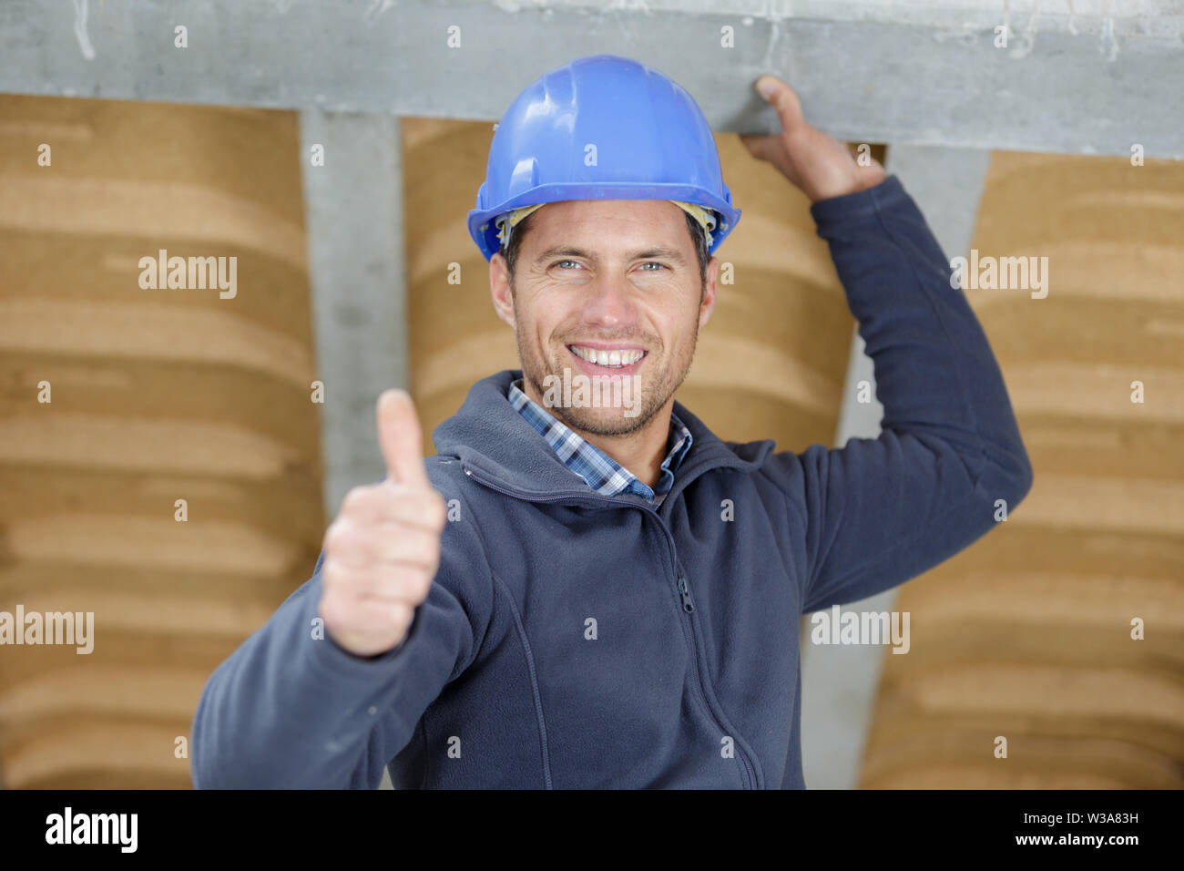 a builder is showing a thumb up - Stock Image
