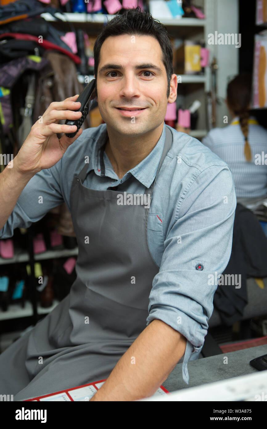 male caucasian cobbler on the telephone - Stock Image