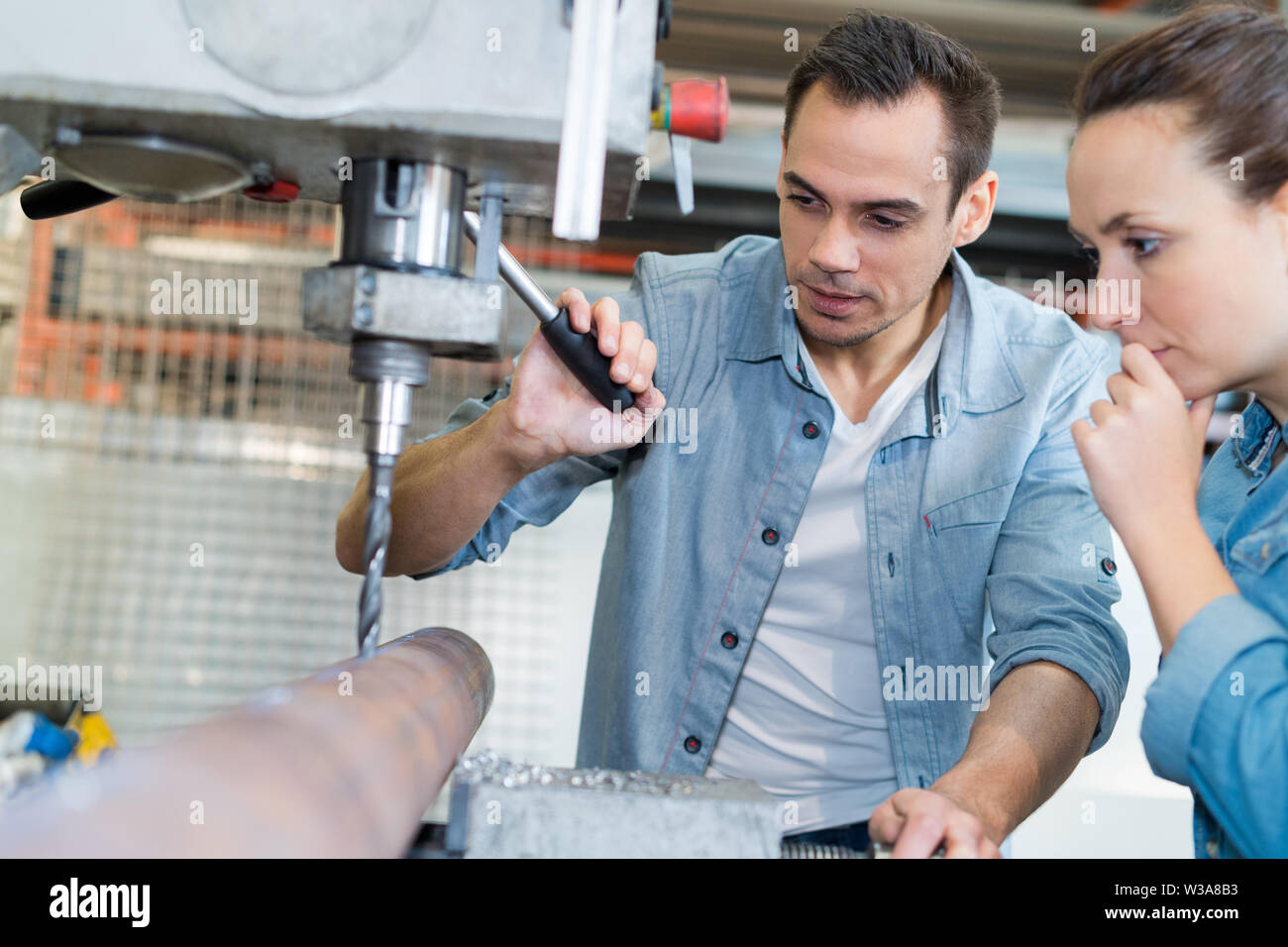 young technicians working on pillar drilling machine in workshop - Stock Image