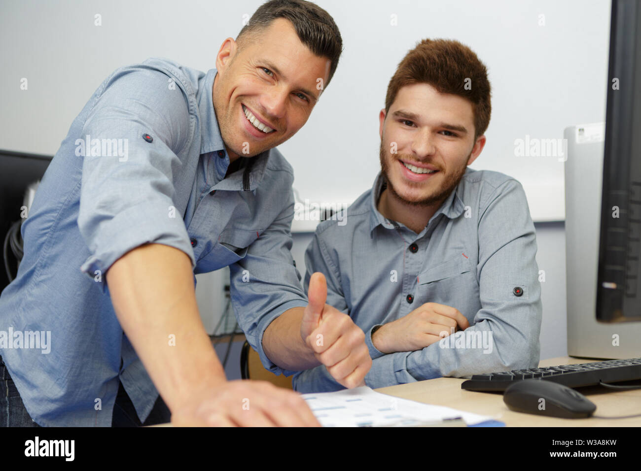 portrait of two happy professional in workshop - Stock Image