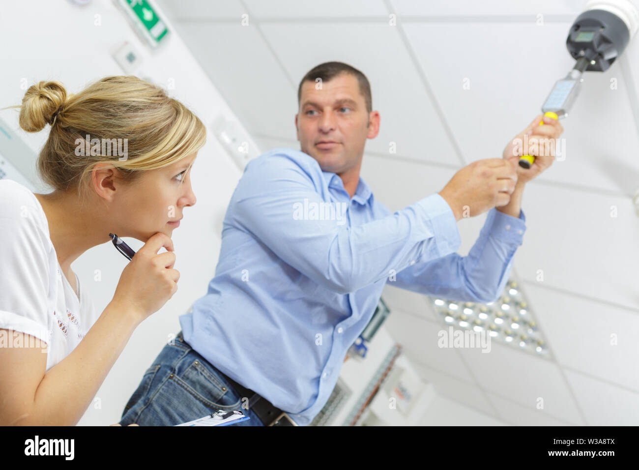 man testing a ceiling mounted detector - Stock Image