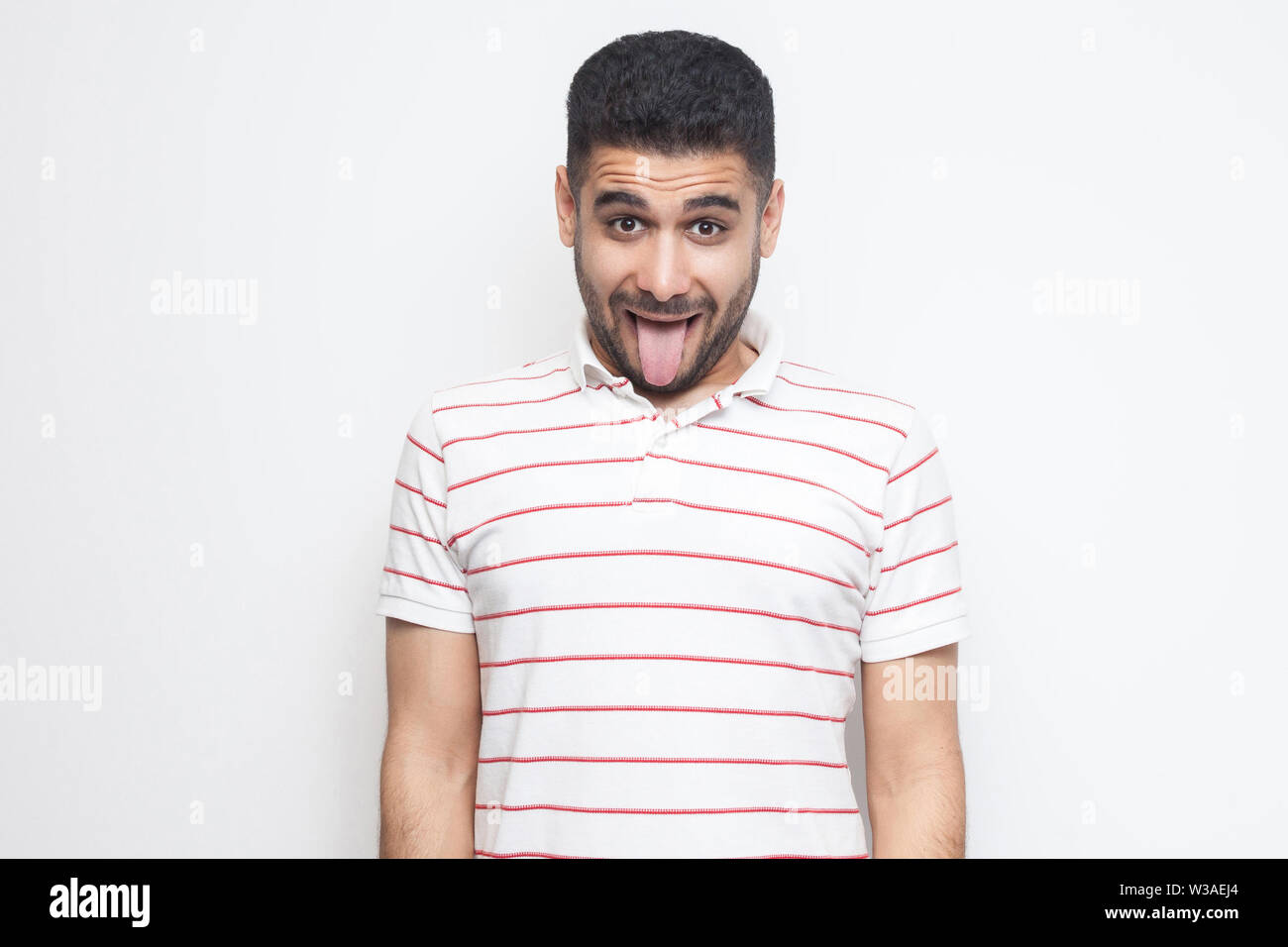 Portrait of funny crazy handsome bearded young man in striped t-shirt standing, tongue out and looking at camera with funny face. indoor studio shot, Stock Photo