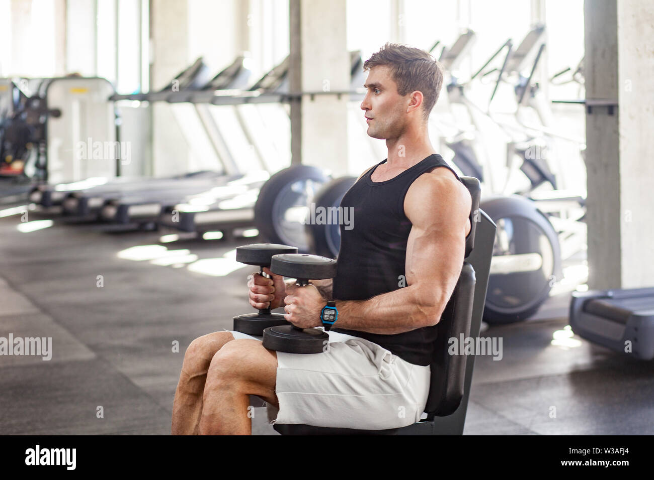 Side view portrait of young adult man muscular built handsome athlete working out in a gym, sitting on bench and holding two dumbbell on the knees. in Stock Photo