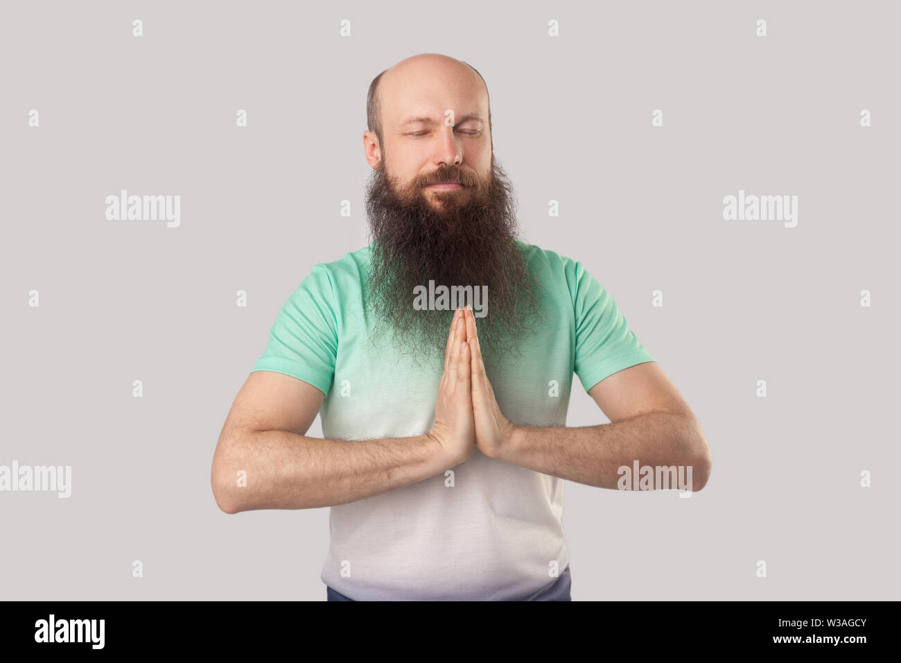 Portrait of calm serious middle aged bald man with long beard in light green t-shirt standing with closed eyes, palm hand and doing yoga meditation. i Stock Photo