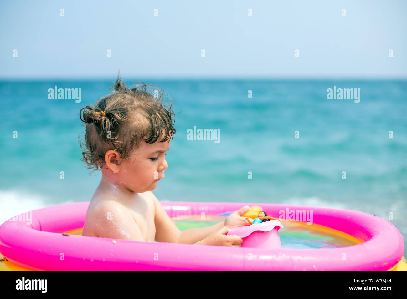 A little girl is playing an inflatable pool. Cute baby in an inflatable pool against the backdrop of the blue sea. Baby-girl bathes her doll - Stock Image