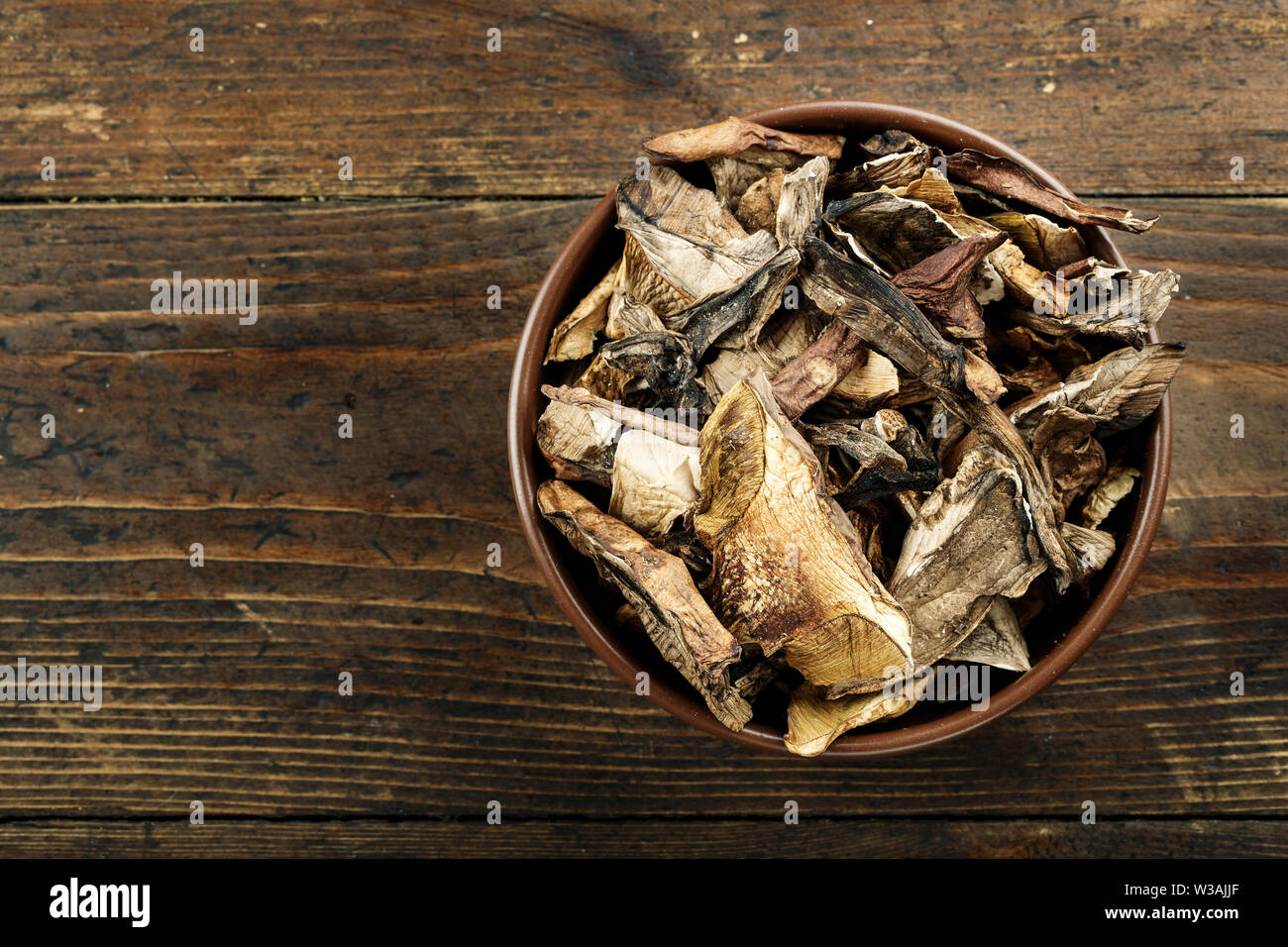 dried mushrooms in a clay plate on a brown wooden table - Stock Image