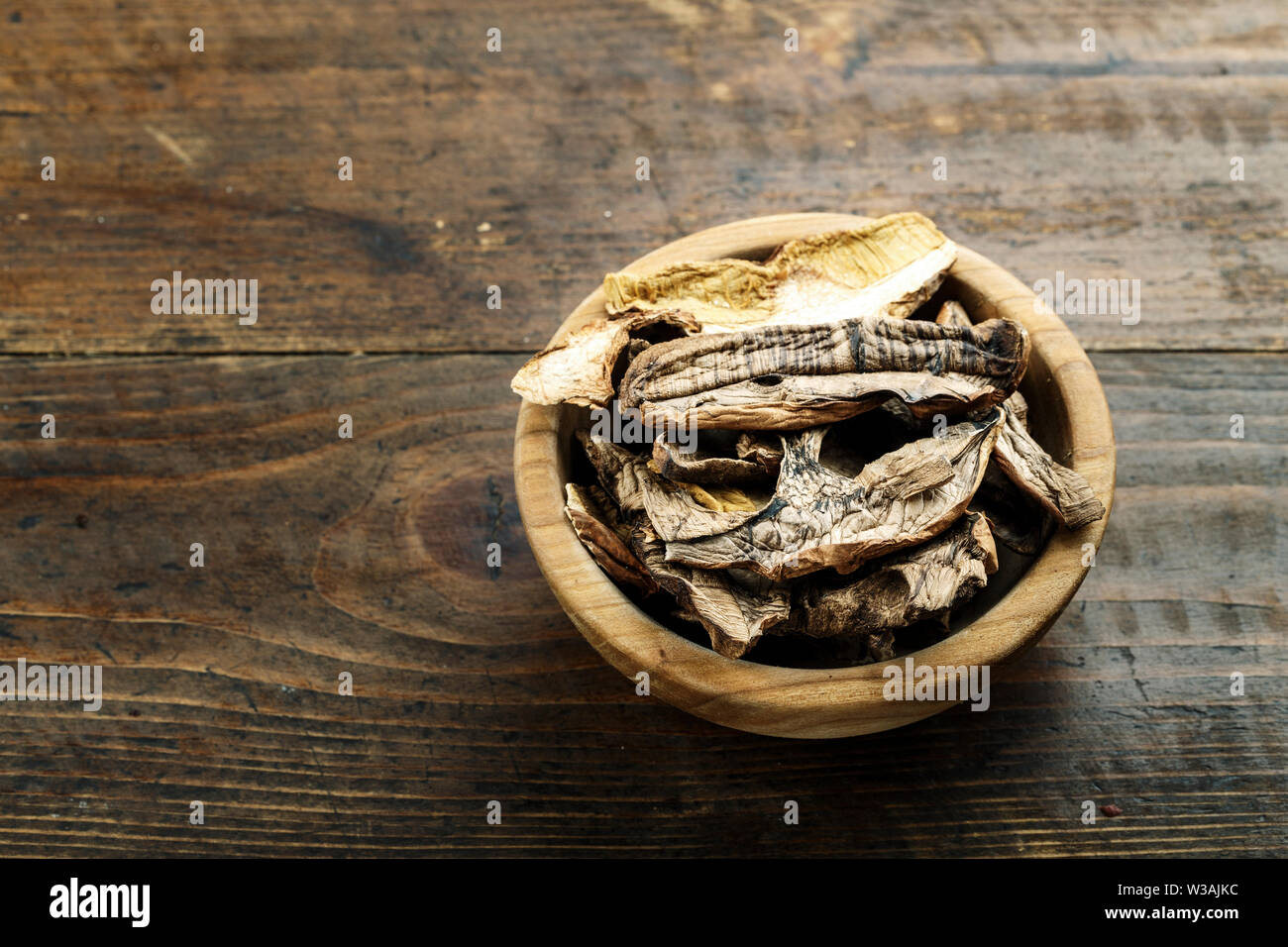 dried mushrooms in a wooden plate on a brown wooden table - Stock Image