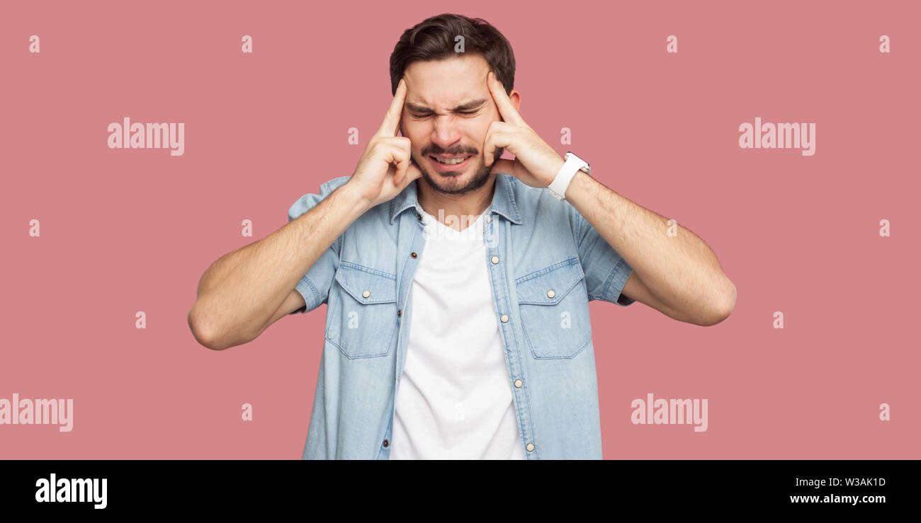 Headache, confusion or thinking. Portrait of sad handsome bearded young man in blue casual shirt standing and holding his head, thinking or endure. in - Stock Image