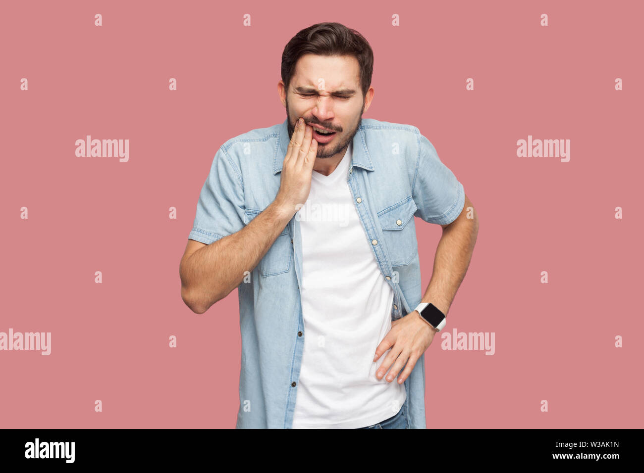 toothache or pain. Portrait of sad sick bearded young man in blue casual style shirt standing and touching his chik because feeling pain on tooth. ind Stock Photo