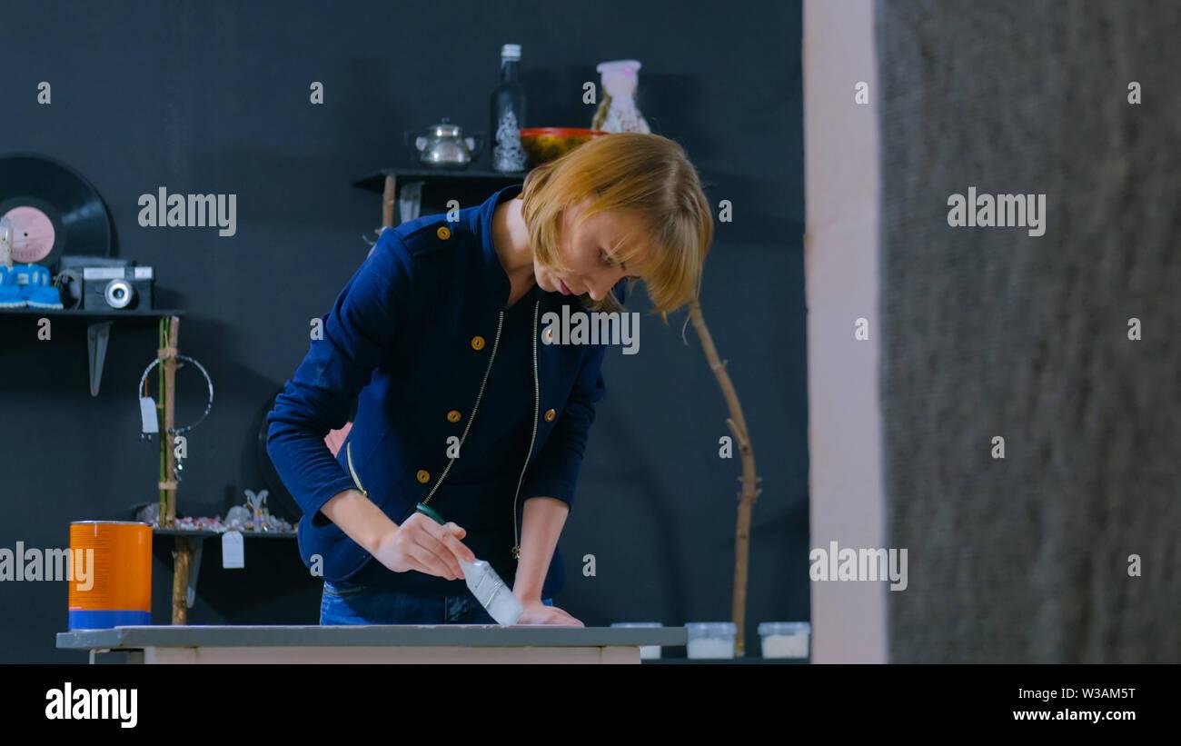 Professional woman decorator, designer painting wooden circle decoration - Stock Image